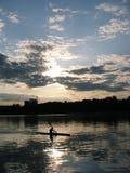 La réflexion du coucher de soleil sur le lac, kayaker photographie stock libre de droits