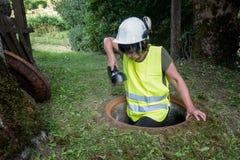 La réparation d'égout fonctionne dans le trou d'homme à côté d'une travailleuse photo libre de droits