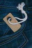 La rétro étiquette de papier de carton avec la chaîne de caractères dans des jeans de denim empochent Photo libre de droits