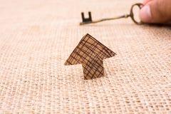 La rétro clé et une flèche ont coupé du papier brun Images stock