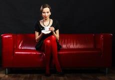 La rétro femme tient la tasse de thé se reposant sur le sofa photos libres de droits