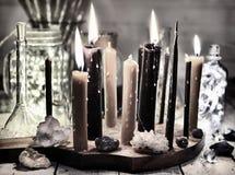 La rétro vie immobile avec brûler les bougies noires, les bouteilles brillantes et les minerais images stock