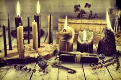 La rétro vie immobile avec les bougies brûlantes, les bougies noires, la clé et l'horloge sur la table en bois photos libres de droits