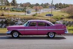 La rétro voiture rose américaine de cru classique de 1959 du proection latéral, a arrangé devant un paysage de village photographie stock libre de droits