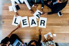 La réunion d'équipe d'affaires avec le mot apprennent sur la table Photo stock