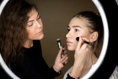La r?flexion dans le miroir du maquilleur la fille avec du charme fait le maquillage ? une belle jeune fille photos stock