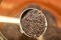 La raccolta del tè a cucchiaiate sciolto copre di foglie da un contenitore - fuoco selettivo fotografia stock libera da diritti