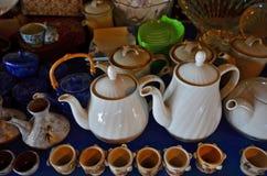 La raccolta della tazza e della teiera mostra sulla tavola Fotografia Stock Libera da Diritti