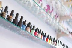 La raccolta di bottiglia variopinta dello smalto del manicure ha messo sullo scaffale Immagini Stock