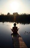 La ragazza è agganciata nella meditazione sul piccolo ponticello Fotografia Stock