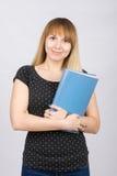 La ragazza è con un sorriso e tiene la cartella con i documenti al suo petto Fotografie Stock