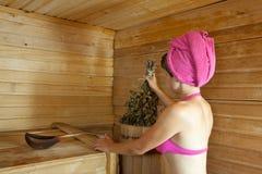 La ragazza è cotta a vapore nella sauna Immagine Stock