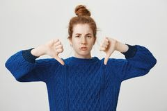 La ragazza è in disaccordo e che la mostra che condanni Colpo dello studio della ragazza europea aggrottante le sopracciglia disp Immagine Stock
