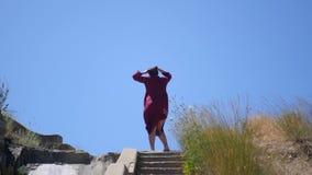 La ragazza è filare, stante sopra le scale, in una corrente di vento contro il cielo e l'erba 3840x2160, 4K video d archivio