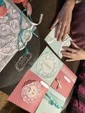 La ragazza è impegnata nella fabbricazione delle cartoline d'auguri a casa Facendo uso di carta, di pizzo, della treccia e di alt immagine stock