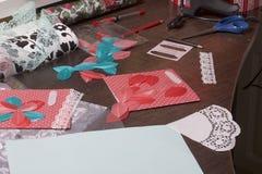 La ragazza è impegnata nella fabbricazione delle cartoline d'auguri a casa Facendo uso di carta, di pizzo, della treccia e di alt fotografie stock libere da diritti