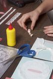 La ragazza è impegnata nella fabbricazione delle cartoline d'auguri a casa Facendo uso di carta, di pizzo, della treccia e di alt immagini stock