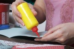 La ragazza è impegnata nella fabbricazione delle cartoline d'auguri a casa Facendo uso di carta, di pizzo, della treccia e di alt immagine stock libera da diritti