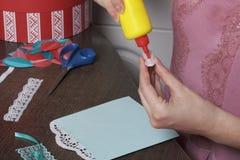 La ragazza è impegnata nella fabbricazione delle cartoline d'auguri a casa Facendo uso di carta, di pizzo, della treccia e di alt fotografie stock
