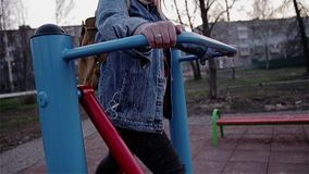 La ragazza è impegnata in un simulatore del piede sul campo da giuoco nel parco della città La macchina fotografica mostra un pan archivi video
