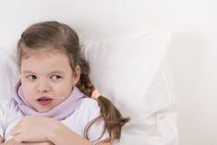 La ragazza è malata ed esamina la destra, con una cucchiaiata del farmaco, trovantesi a letto Fotografia Stock