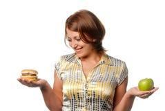 La ragazza è scelta fra la mela e l'hamburger Fotografia Stock Libera da Diritti