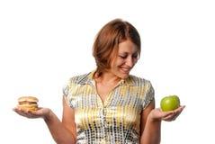 La ragazza è scelta fra la mela e l'hamburger Immagine Stock