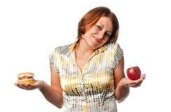 La ragazza è scelta fra la mela e l'hamburger Immagini Stock