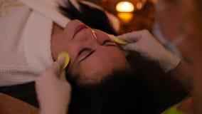 La ragazza è spalmata di crema nel fronte nel salone di bellezza stock footage