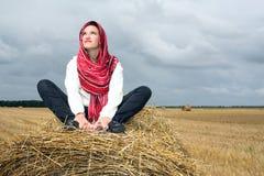 La ragazza è su una pila della paglia Fotografie Stock Libere da Diritti