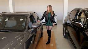 La ragazza è su una sala d'esposizione moderna fra le automobili costose, lei sceglie una nuova automobile stock footage