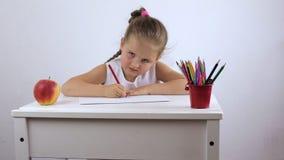 La ragazza è un bambino in età prescolare che si siede allo scrittorio e diligente esegue il compito archivi video