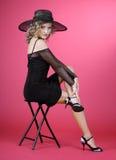 La ragazza è in un cappello su colore rosso Fotografia Stock