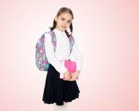 La ragazza è una scolara con un libro in sue mani Fotografia Stock