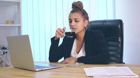La ragazza è vestita in vestiti alla moda che si siedono all'ufficio e stampa un documentario archivi video