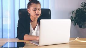 La ragazza è vestita in vestiti alla moda, sedentesi nell'ufficio e stampanti un documentario video d archivio