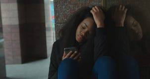 La ragazza abbastanza africana isolata depressa con vista triste sta ascoltando musica tramite cuffie mentre si sedeva sul archivi video