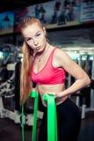 La ragazza abbastanza atletica con capelli biondi lunghi utilizza la banda verde di allungamento mentre si esercita in palestra Fotografia Stock