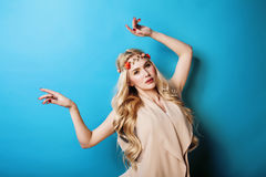 La ragazza abbastanza bionda dei giovani con capelli biondi ricci e piccolo abbassa sorridere felice sul fondo del cielo blu Fotografie Stock