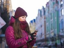 La ragazza abbastanza castana che porta il cappotto, il cappello porpora e la sciarpa dell'inverno, camminanti dalla via europea  Immagini Stock Libere da Diritti