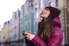 La ragazza abbastanza castana che porta il cappotto, il cappello porpora e la sciarpa dell'inverno, camminanti dalla via europea  Fotografie Stock Libere da Diritti