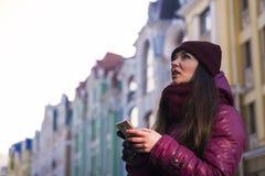 La ragazza abbastanza castana che porta il cappotto, il cappello porpora e la sciarpa dell'inverno, camminanti dalla via europea  Fotografie Stock