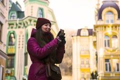 La ragazza abbastanza castana che porta il cappotto, il cappello porpora e la sciarpa dell'inverno, camminanti dalla via europea  Fotografia Stock