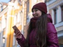 La ragazza abbastanza castana che porta il cappotto, il cappello porpora e la sciarpa dell'inverno, camminanti dalla via europea  Immagine Stock Libera da Diritti