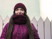 La ragazza abbastanza castana che porta il cappotto, il cappello porpora e la sciarpa dell'inverno, camminanti dalla via europea  Immagine Stock