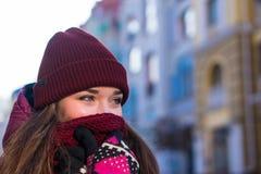 La ragazza abbastanza castana che porta il cappotto, il cappello porpora e la sciarpa dell'inverno, camminanti dalla via europea  Immagini Stock