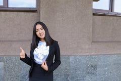 La ragazza abbastanza diligente dello studente esamina diritto la macchina fotografica, tiene Thu Immagine Stock