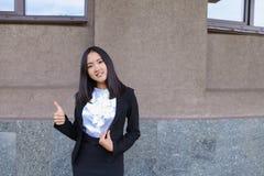 La ragazza abbastanza diligente dello studente esamina diritto la macchina fotografica, tiene Thu Immagini Stock