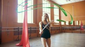 La ragazza abbastanza flessibile dei giovani si prepara con un nastro verde - esercizio della ginnastica in studio con lo specchi video d archivio