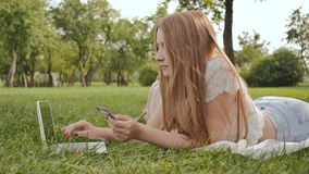 La ragazza abbastanza giovane dello studente rende gli acquisti online facendo uso di una carta di credito e di un computer porta stock footage
